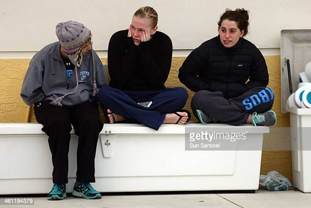 Swimmers from the Tufts University swim team Simonne Dubois from left Emma Vanlieshout and Maddie Golison try to keep warm after getting out of the...