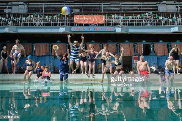 Swimmers jump into the pool at Victoria Baths which are opening today for the first time in over 20 years for a one off public swimming event on May...