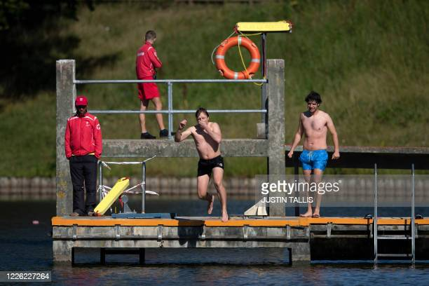 Swimmers jump into the water at the Hampstead Heath men's bathing pond in London on July 11 as restrictions are further eased during the novel...