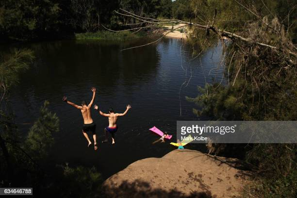 Swimmers jump off a rock into the river to escape the heat at the Nepean River Reserve in Menangle Park on February 11 2017 in Sydney Australia With...