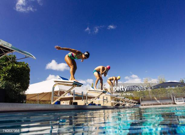 Swimmers on pool diving board