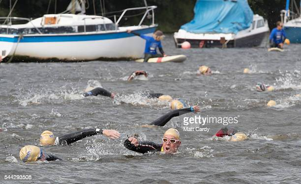Swimmers participate in the Outdoor Swimming Society's annual Bantham Swoosh as they swim on the river Avon towards the finish at Bantham Beach on...