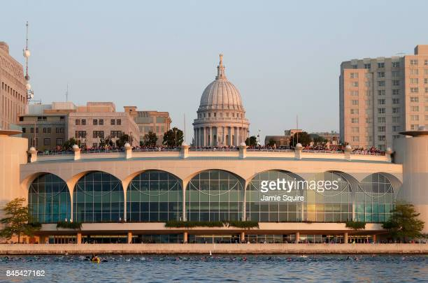 Swimmers pass in front of Monona Terrace as the state capitol is seen in the background during the Ironman Madison on September 10 2017 in Madison...