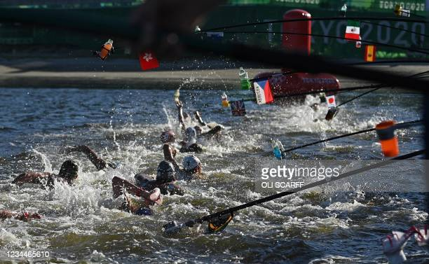 Swimmers pass the refuelling station as they compete in the men's 10km marathon swimming event during the Tokyo 2020 Olympic Games at the Odaiba...