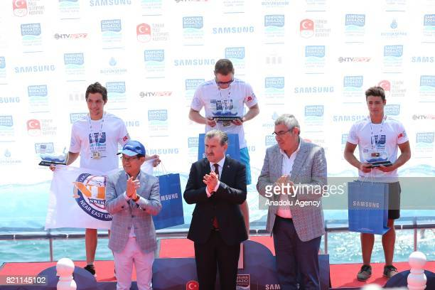 Swimmers ranked in 1st Evgeny Eliseev 2th Dogukan Uluc and 3th Erge Can Gezmis stand as Turkey's new Youth and Sports Minister Osman Askin applauds...
