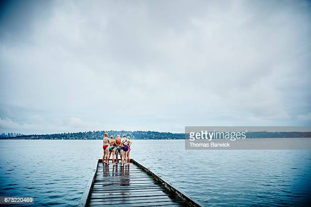 Swimmers standing on dock before morning swim