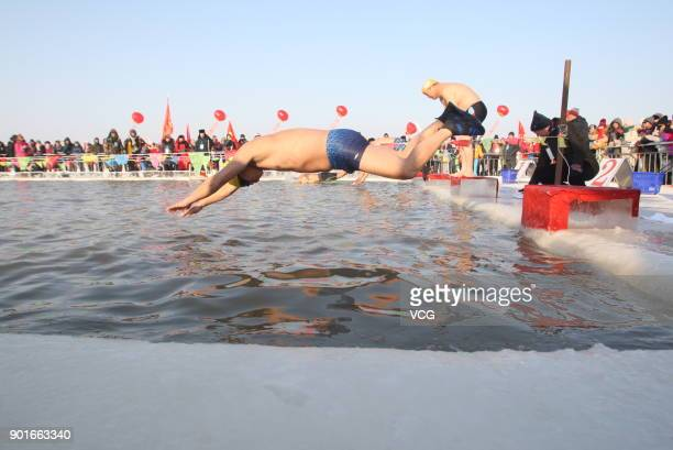 Swimmers take part in the 18th International Winter Swimming Invitational Competition at a pool carved up from the frozen Songhua river during the...