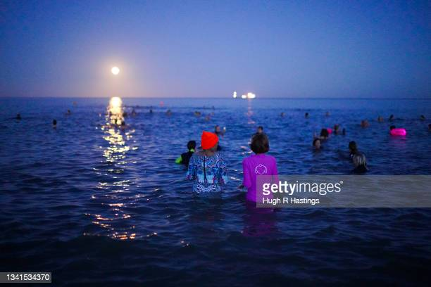 Swimmers take to the sea to swim under the Harvest Moon on September 20, 2021 in Swanpool Beach, Falmouth, England.