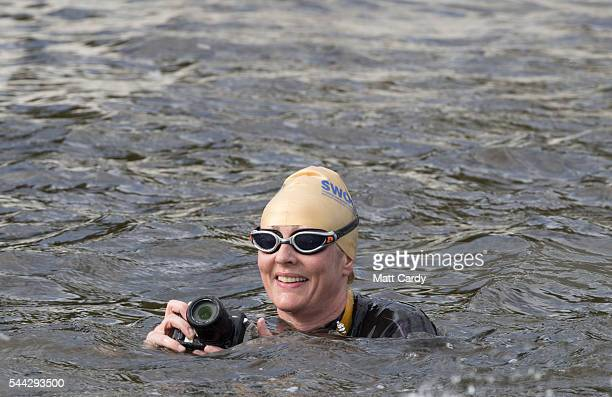 A swimmers takes a photograph as she participates in the Outdoor Swimming Society's annual Bantham Swoosh as she swims on the river Avon towards the...