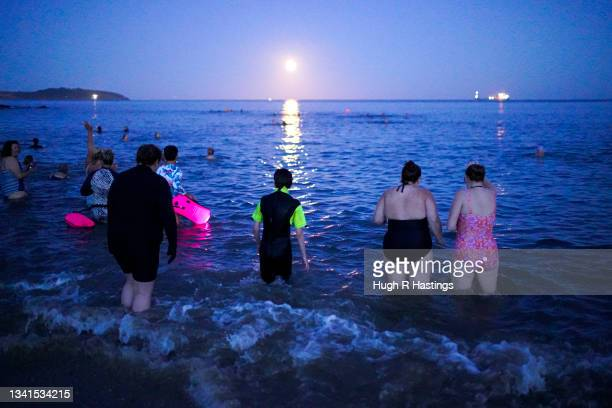 Swimmers takes to the sea to swim under the Harvest Moon on September 20, 2021 in Swanpool Beach, Falmouth, England.
