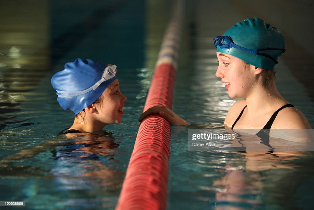 Swimmers talking in pool lanes : Stock Photo
