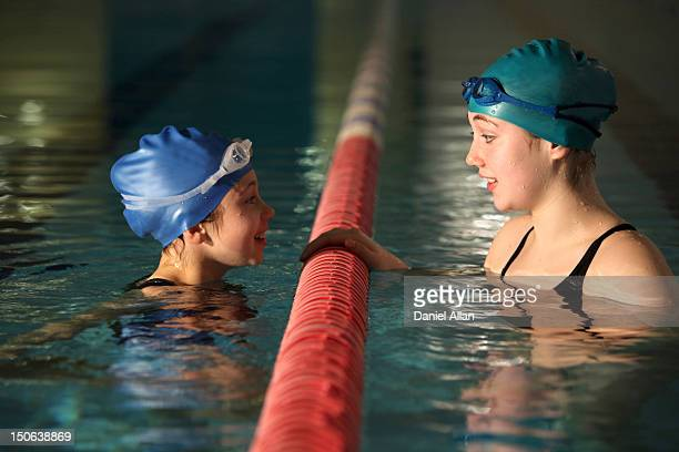 swimmers talking in pool lanes - length stock pictures, royalty-free photos & images