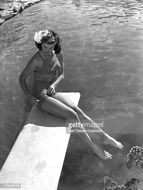 Swimming champion and future movie star Esther Williams poses for a portrait on the diving board of the pool at the Beverly Hills Hotel in 1939 in...