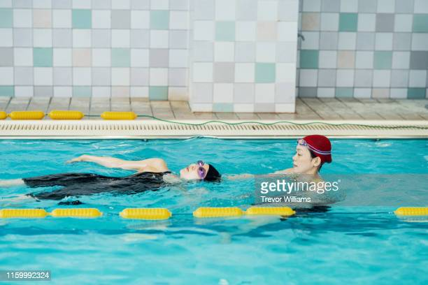 Swimming coach working with a disabled woman who is training for competition