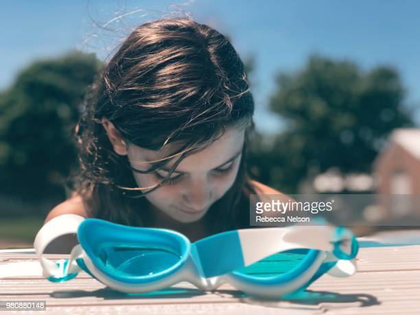 swimming goggles at swimming pool's edge with girl in background