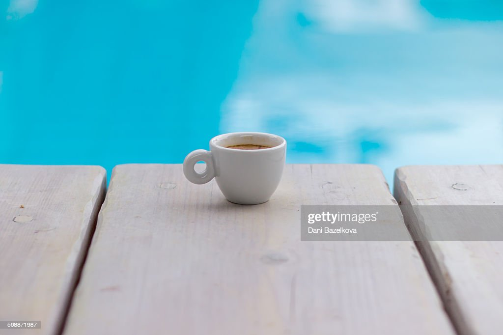 Swimming pool and cup of coffee on wooden deck : Stock Photo