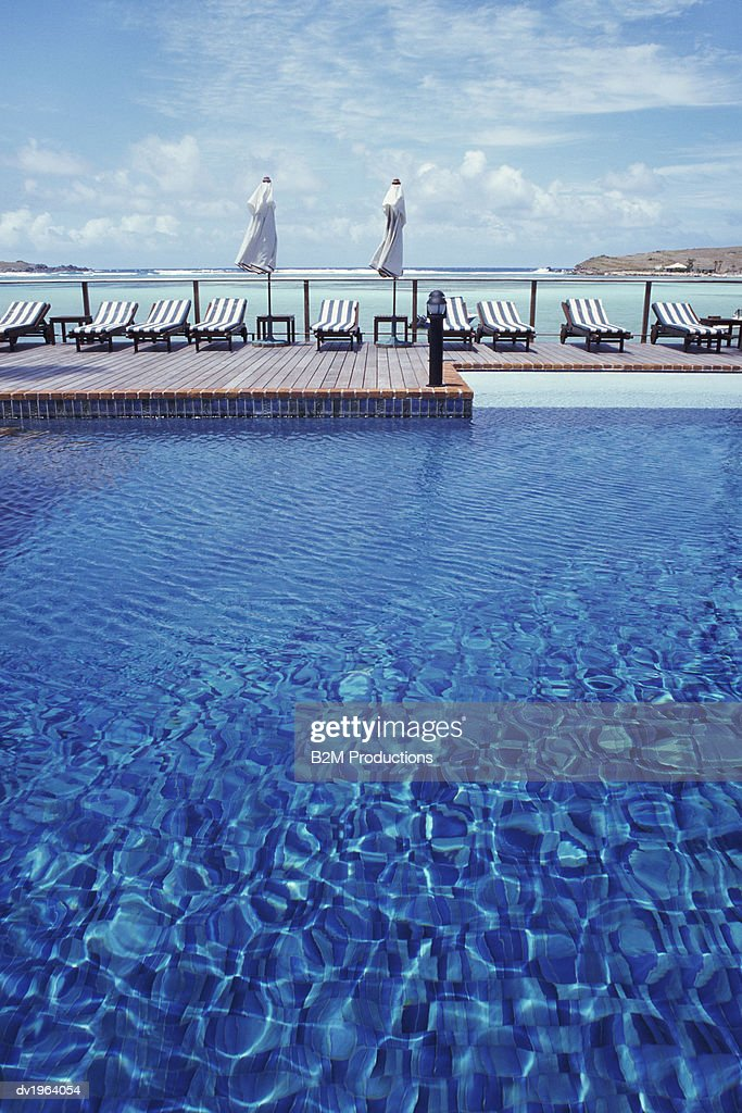 Swimming Pool and Sun Loungers by the Coast : Stock Photo