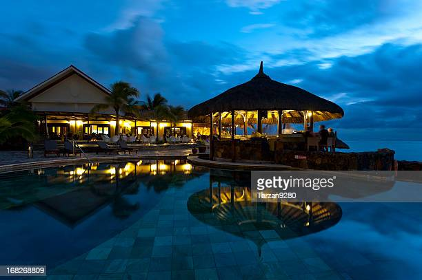 A swimming pool at night showing reflections of the bar
