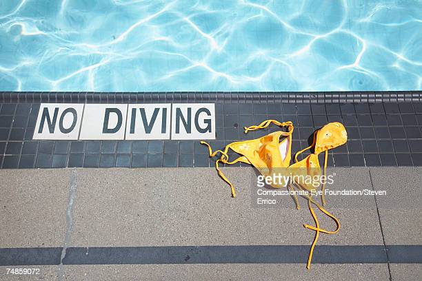 Swimming pool, bikini discarded next to No Diving sign on ground, elevated view