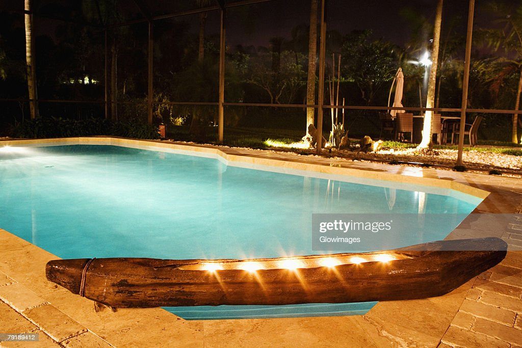 Swimming pool lit up at night : Stock Photo
