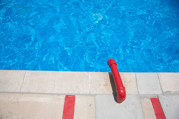 A swimming pool with a red water pipe