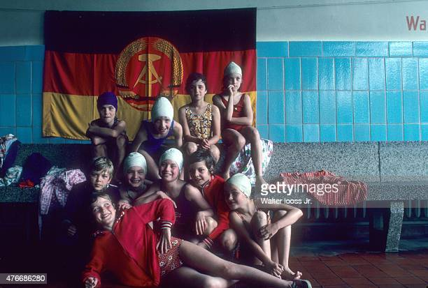 Portrait of youth athletes posing in front of East Germany flag during photo shoot outside pool East Germany 6/7/1976 CREDIT Walter Iooss Jr