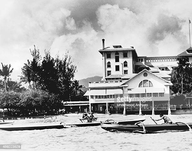 Swimming star Duke Kahanamoku wins the one man canoe championship in his long black and white outrigger crossing the finish line in front of the...