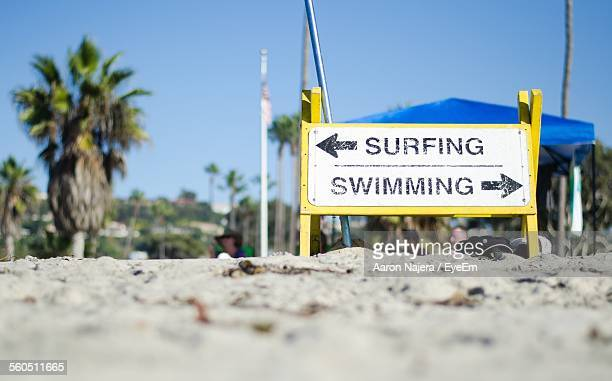 Swimming With Surfing Sign On Beach