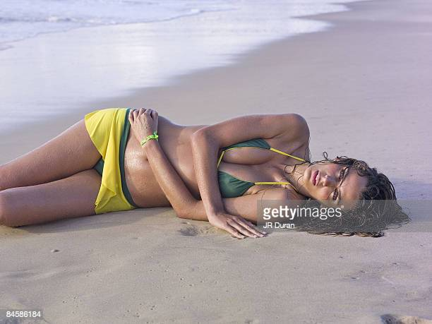 Swimsuit 2007 Issue Portrait of Fernanda Motta lying on beach at Txai Resort Bahia Bikini by Delfina Swimwear