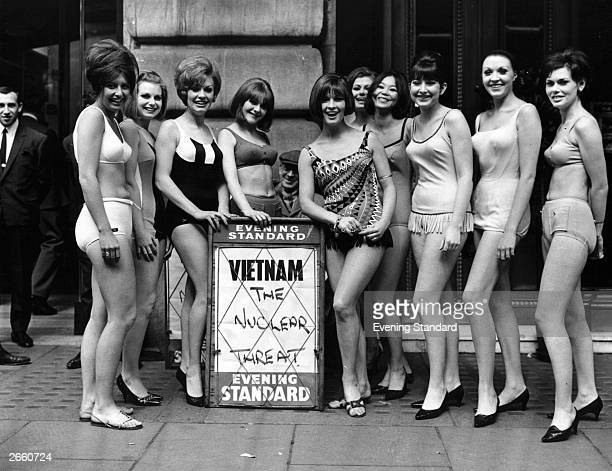 Swimsuit models posing for the camera in London, by an Evening Standard newspaper vendor's board announcing 'Vietnam, The Nuclear Threat'.
