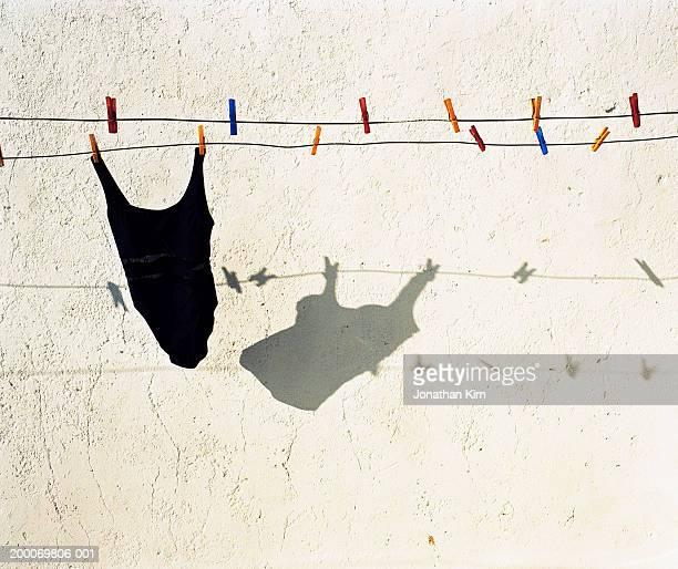 swimsuit on clothesline casting shadow on stucco wall - maillot de bain photos et images de collection