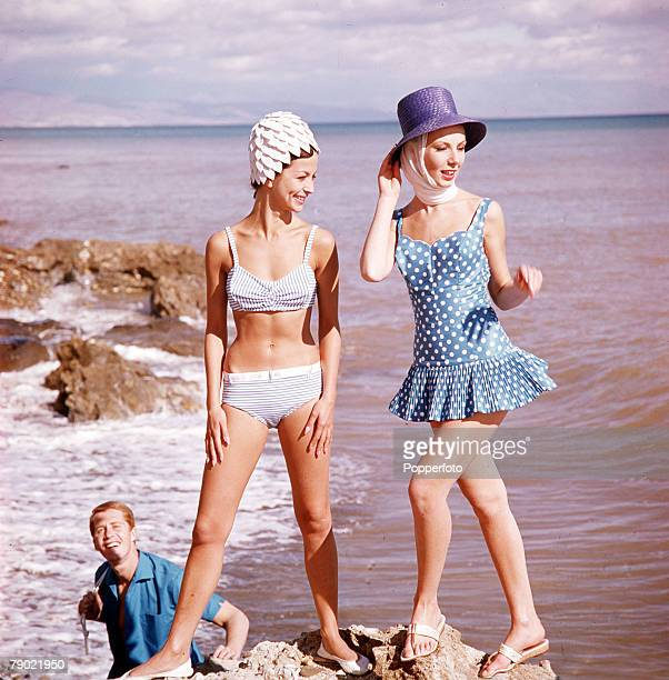 1963 Swimwear Two attractive young women one wearing a white petal swimcap and a bikini the other wearing a straw hat and blue and white polkadot...