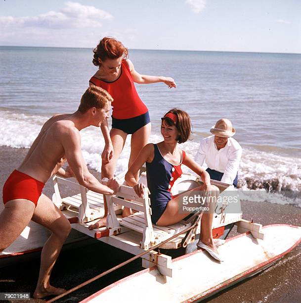 1963 Swimwear Two attractive young women wearing colourful swimwear smile as they sit on a pedalo as they are about to be pushed into the sea by a...