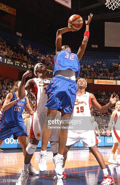 Swin Cash of the Detroit Shock goes to the basket against Taj McWilliamsFranklin and Asjha Jones of the Connecticut Sun in game three of the WNBA...