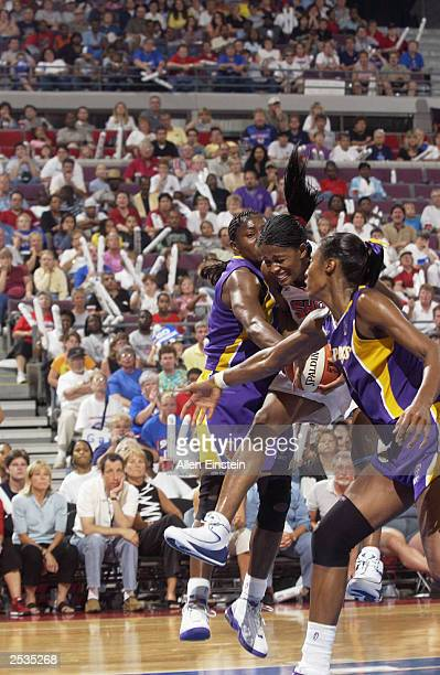 Swin Cash of the Detroit Shock goes up for a shot under pressure from Lisa Leslie and Mwadi Mabika of the Los Angeles Sparks during game two of the...