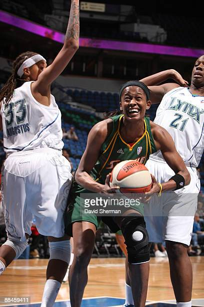 Swin Cash of the Seattle Storm pushes through towards the basket against Seimone Augustus and Nicky Anosike of the Minnesota Lynx on June 12 2009 at...