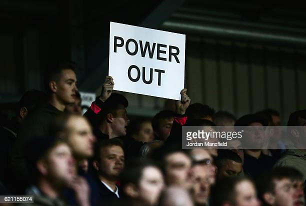 Swindon Town fan show his feelings towards chairman Lee Power as he holds a 'Power out' banner during The Emirates FA Cup first round match between...