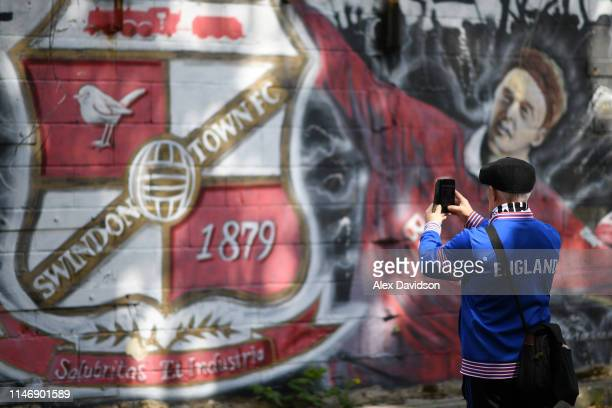 Swindon Town fan takes a photo of a Mural prior to the Sky Bet League Two match between Swindon Town and Notts County at County Ground on May 04 2019...