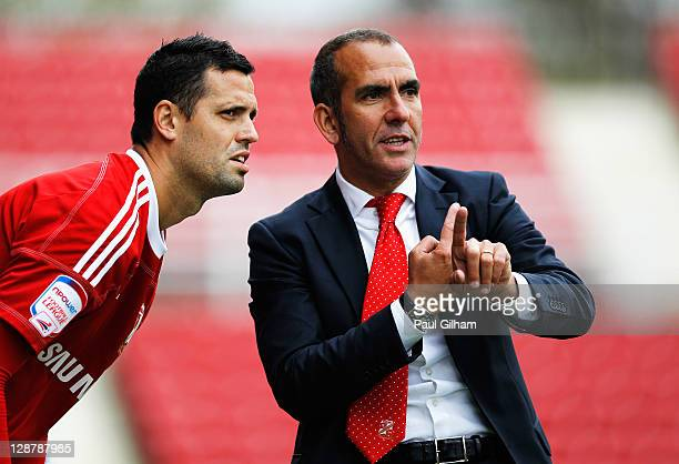 Swindon Town manager Paulo Di Canio talks to Lukas Magera during the npower League Two match between Swindon Town and Hereford United at the County...