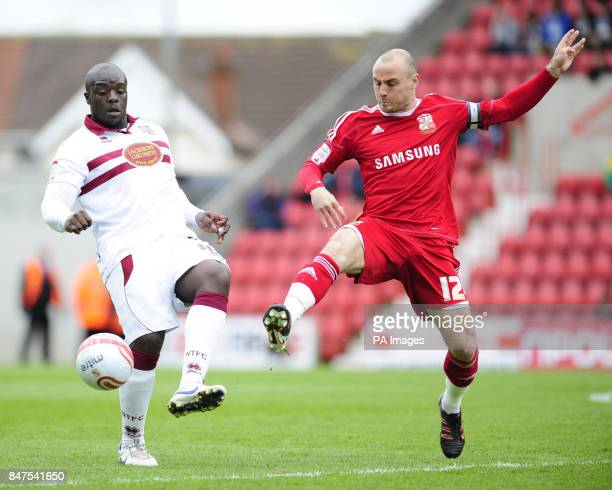 Swindon Town's Alan McCormack and Northampton Town's Adebayo Akinfenwa battle for the ball during the npower Football League Two match at the county...