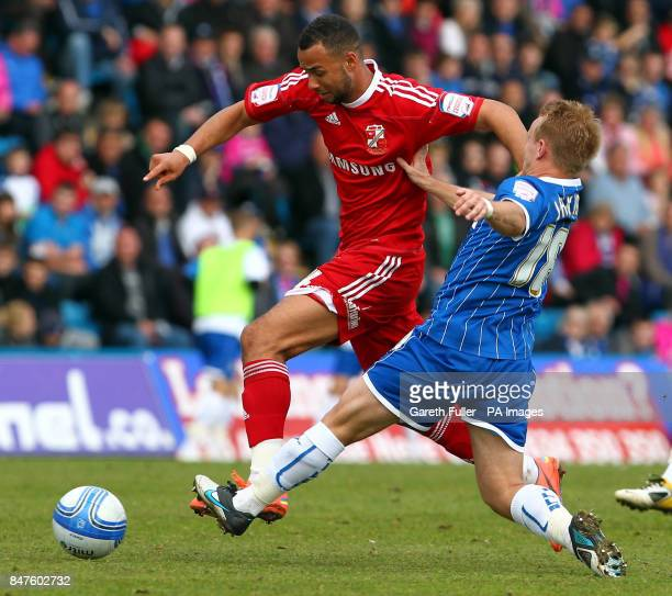 Swindon's John Bostock is challenged by Gillingham's Danny Jackman during the League Two match at the MEMS Priestfield Stadium Gillingham