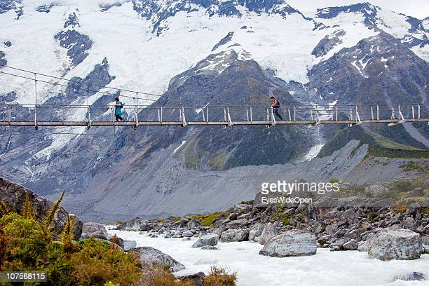 Swing bridge with hikers walking in the Hooker Valley on a track to Hooker Glacier on December 12 2010 in Aoraki / Mount Cook National Park South...
