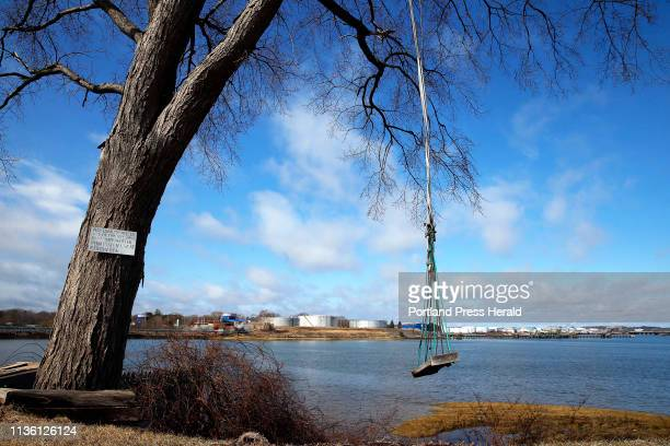 A swing on Elm Street in South Portland's Pleasantdale neighborhood sways in the breeze while petroleum tanks loom upstream on the banks of the Fore...