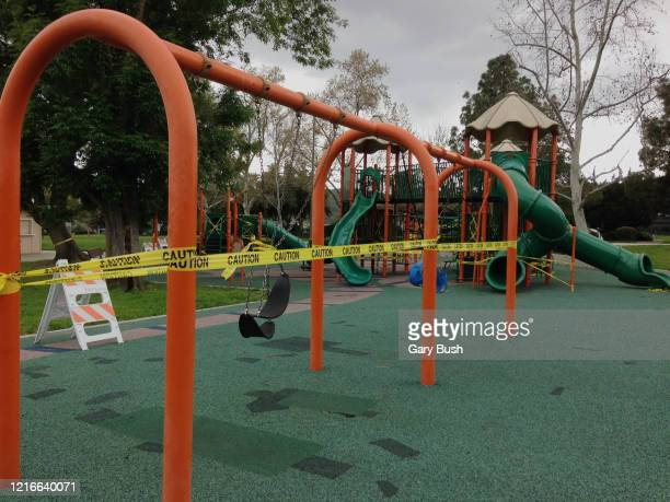 swing set wrapped in caution tape in closed play area due to coronavirus pandemic - アゴーラヒルズ ストックフォトと画像