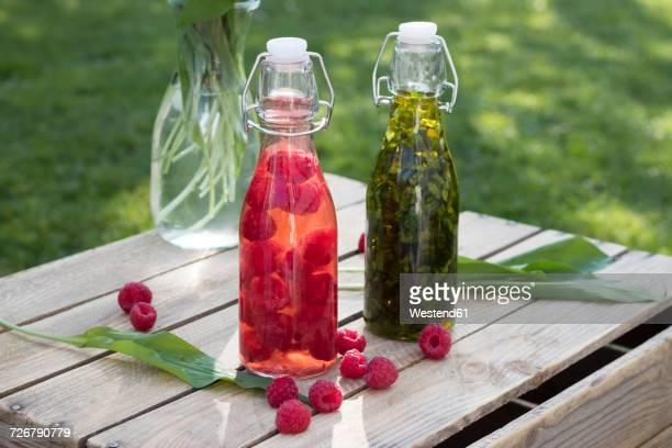 Swing top bottles of chopped ramson in olive oil and raspberries in wine vinegar