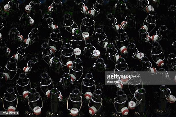 Swing top lids hang from open bottles of Grolsch beer inside the Grolsch brewery operated by SABMiller Plc in Enschede Netherlands on Monday April 25...