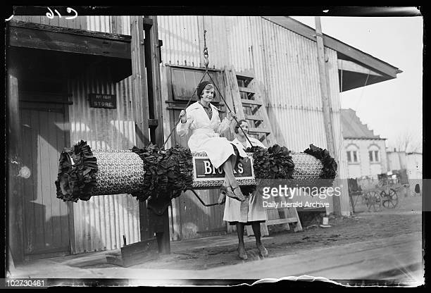 Swinging on a festive 'firework' 1932 A photograph of a woman swinging on a giant festive 'firework' at CT Brocks' factory in Cheam Surrey taken by...