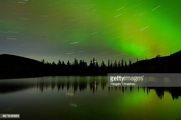 Swirling stars and aurora borealis at Polygonal Lakes at night, Khibiny mountains, Kola Peninsula, Russia