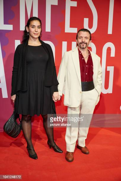 Swiss actor David Bennent and his girlfriend Kavita Chohan pose on the red carpet during the opening of the 23rd Hamburg Film Festival in Hamburg...