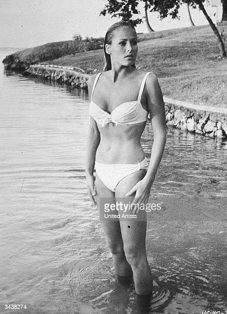 Swiss actor Ursula Andress wears a bikini while standing in water near the shore in a still from the James Bond film 'Doctor No' directed by Terence...